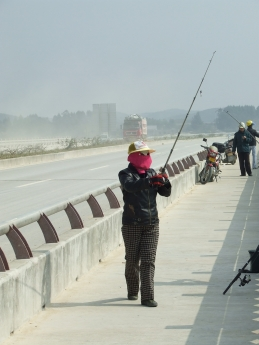 Woman fishing in mask on bridge over Luerhuan River - Dec 2009