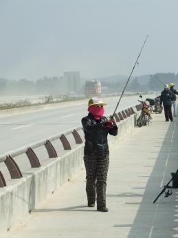 Woman fishing in mask on bridge over Luerhuan River - Dec 2009