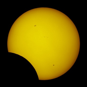 ISS passing across face of sun during partial solar eclipse